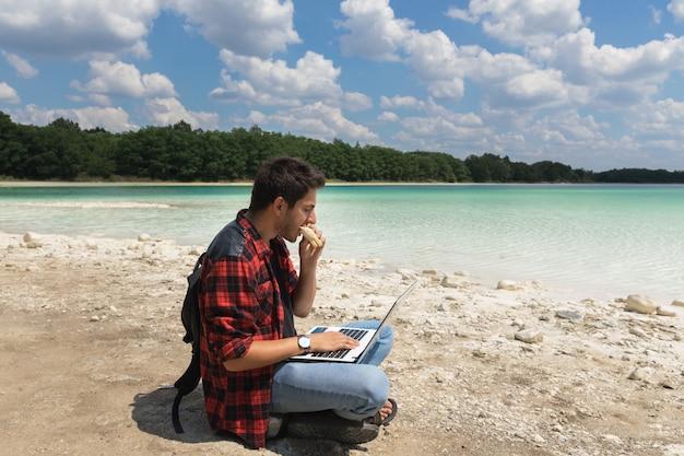 Junger brunettemann in den jeans und im hemd arbeitet an einem computer beim sein auf der natur.