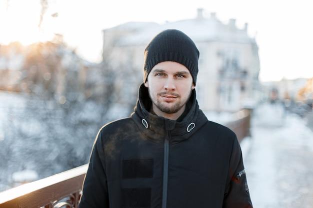 Junger brutaler mann mit einem bart in einem schwarzen stilvollen hut in einer winterjacke auf winterbäumen in der stadt. attraktiver typ.