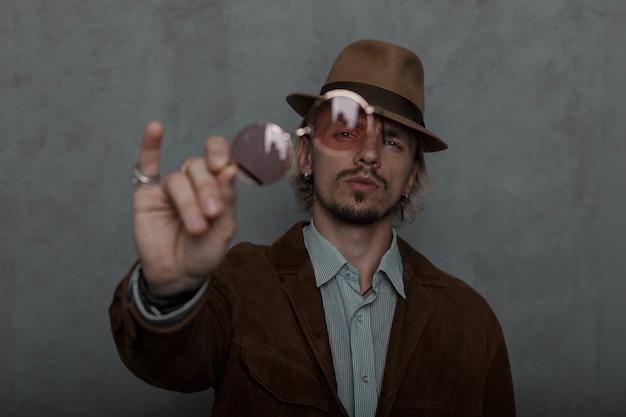 Junger brutaler mann zeigt auf der kamera trendige rote runde brille. modisches kerlmodell in den vintage-kleidern in eleganten retro-hut-posen