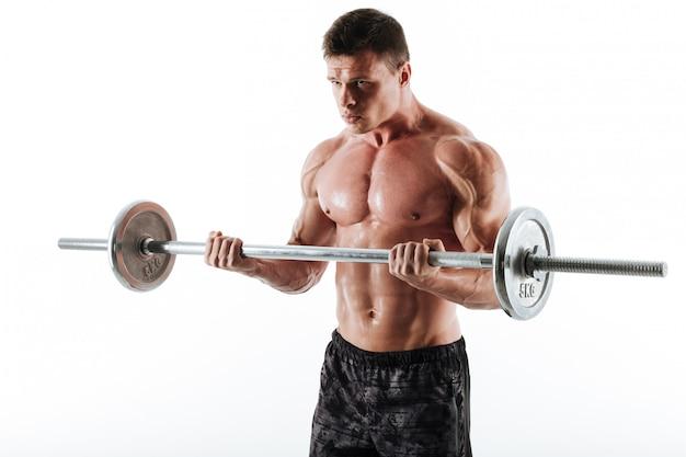 Junger brutaler muskulöser mann, der mit langhantel trainiert und beiseite schaut