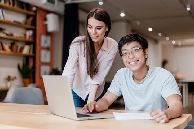 Junger büroangestelltermann und -frau, die an laptop arbeitet