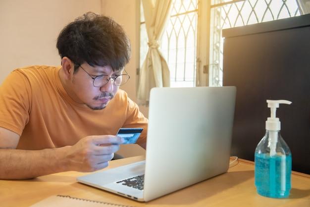 Junger businees mann mit brille, die mit kreditkarte ernsthaft aussieht, um transaktionen durchzuführen, online einzukaufen, an laptops zu hause zu arbeiten, das krisenereignis des koronavirus, covid19