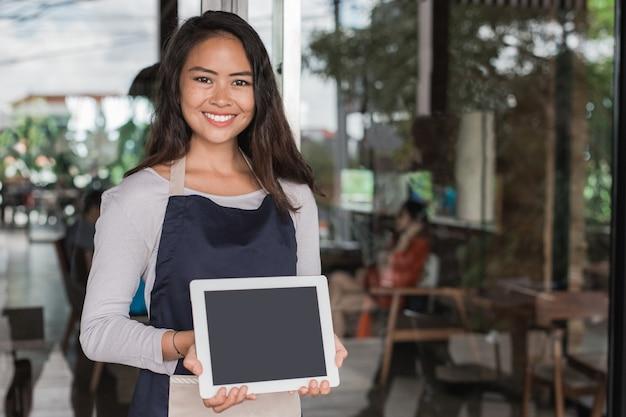 Junger cafébesitzer mit tablette, die vor ihrem geschäft steht