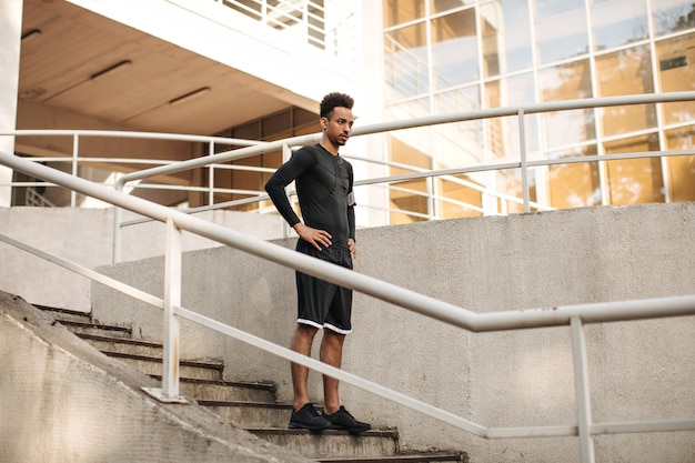 Junger charmanter brünetter dunkelhäutiger mann in shorts und schwarzem langärmeligem t-shirt, der draußen die treppe hinuntergeht