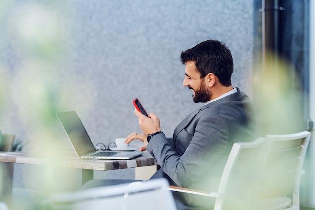 Junger charmanter kaukasischer bärtiger geschäftsmann, der auf terrasse des cafés sitzt und auf nachricht auf social media antwortet. kaffeepause.