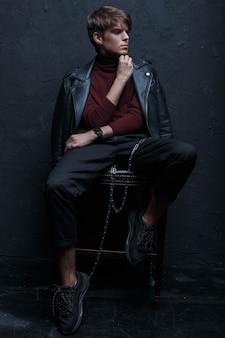 Junger charmanter mann mit einer frisur in einer retro-jacke im roten golf in stilvollen jeans in schwarzen turnschuhen mit einer silbernen metallkette sitzt und posiert auf einem holzstuhl in einem dunklen studio. stilvoller typ