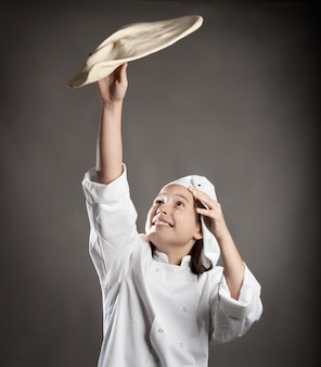 Junger chef, der den teig für pizza bearbeitet