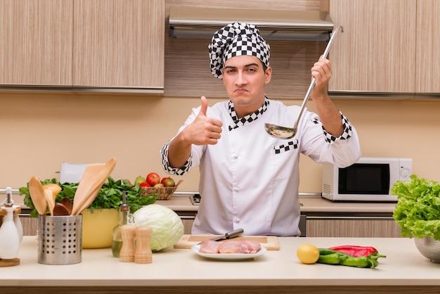 Junger chef, der in der küche arbeitet