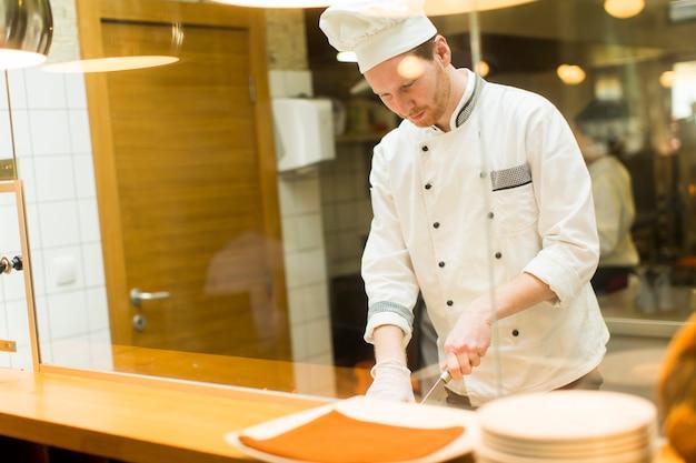 Junger chef, der lebensmittel in der küche zubereitet