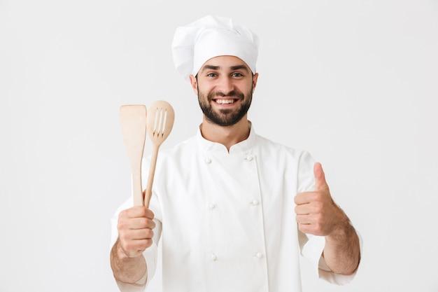 Junger chef in kochuniform, der lächelt, während er hölzerne küchenutensilien isoliert über weißer wand hält?