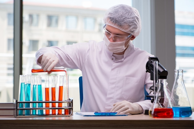 Junger chemiker, der im labor arbeitet