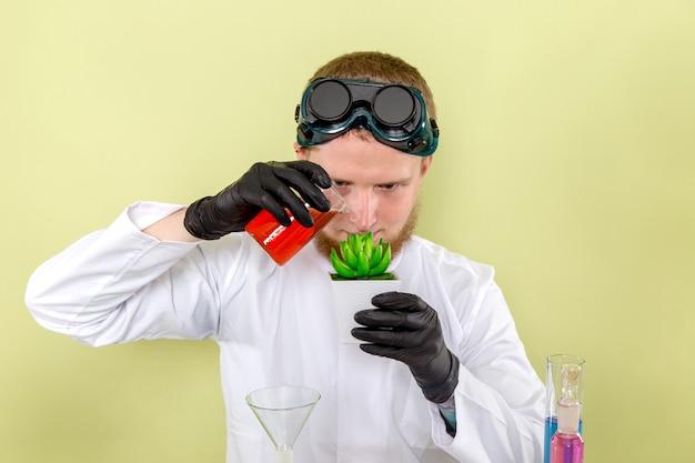Junger chemiker der vorderansicht, der ein experiment mit pflanze macht