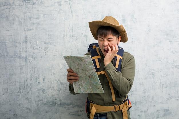 Junger chinesischer entdecker, der eine karte hält, die etwas fröhliches nach vorne schreit