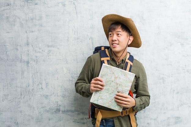 Junger chinesischer forschermann, der ein kartenlächeln überzeugt hält und die arme, oben schauend kreuzt