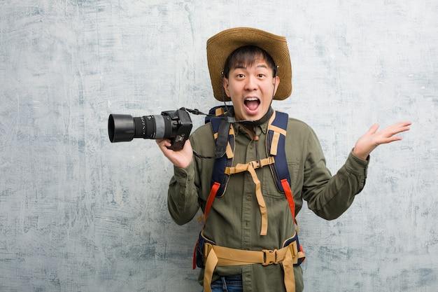 Junger chinesischer forschermann, der eine kamera feiert einen sieg oder einen erfolg hält