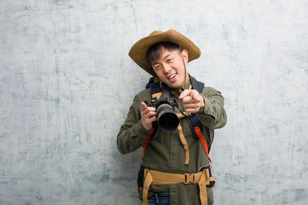 Junger chinesischer forschermann, der eine kamera nett und lächelnd hält, zeigend auf front
