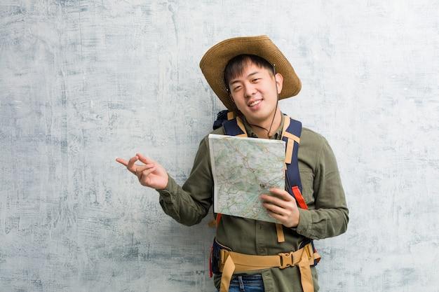 Junger chinesischer forschermann, der eine karte zeigt auf die seite mit dem finger hält