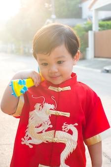 Junger chinesischer junge, der im chinesischen kostümkleid des neuen jahres lächelt und glücklich ist