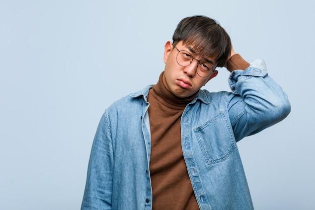 Junger chinesischer mann besorgt und überwältigt