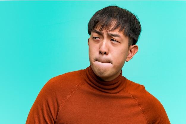 Junger chinesischer mann, der an eine idee denkt