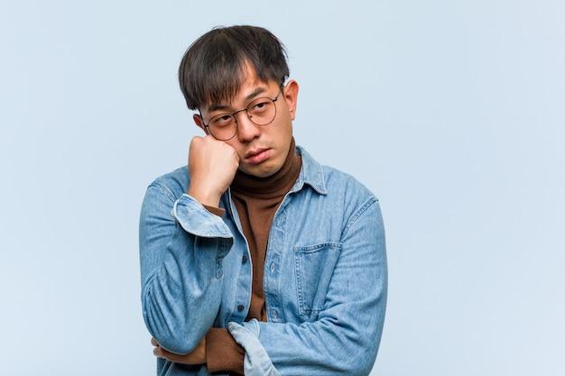 Junger chinesischer mann, der an etwas, schauend zur seite denkt