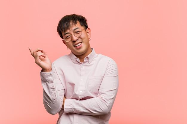 Junger chinesischer mann, der auf die seite mit dem finger zeigt
