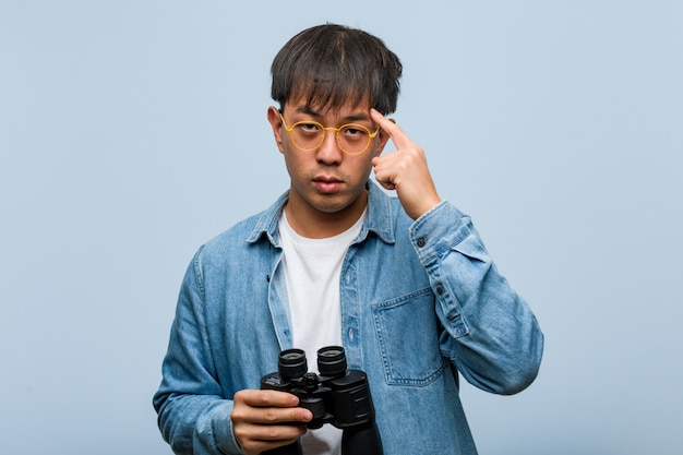 Junger chinesischer mann, der die ferngläser denken an eine idee hält