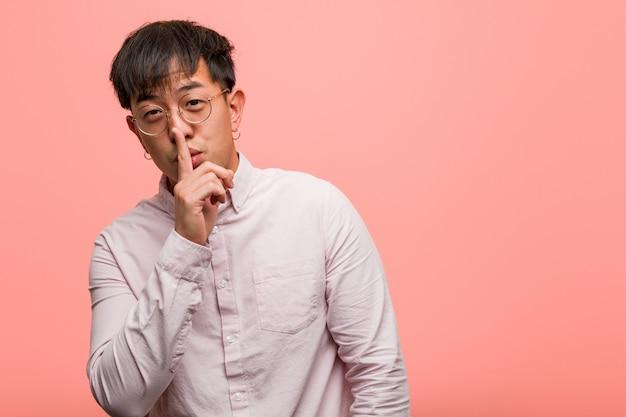 Junger chinesischer mann, der ein geheimnis hält oder um ruhe bittet
