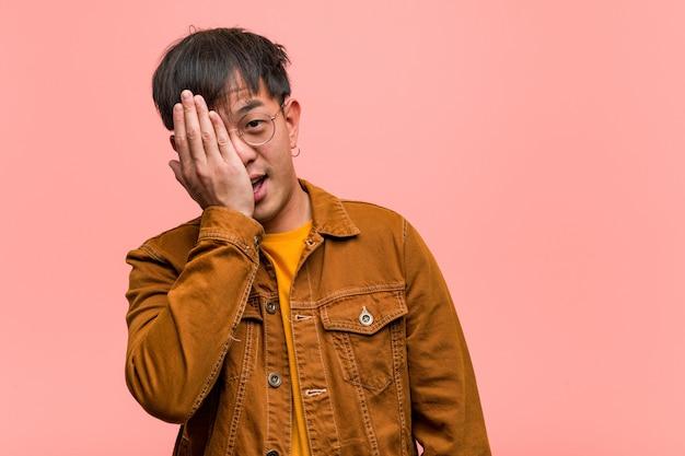 Junger chinesischer mann, der ein jackenschreien glücklich und bedeckungsgesicht mit der hand trägt
