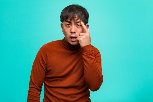 Junger chinesischer mann, der eine enttäuschungsgeste mit dem finger tut