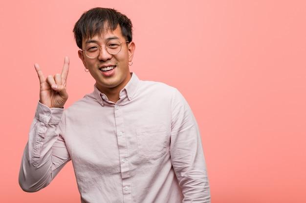 Junger chinesischer mann, der eine felsengeste tut