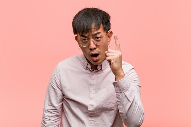 Junger chinesischer mann, der eine idee, inspirationskonzept hat