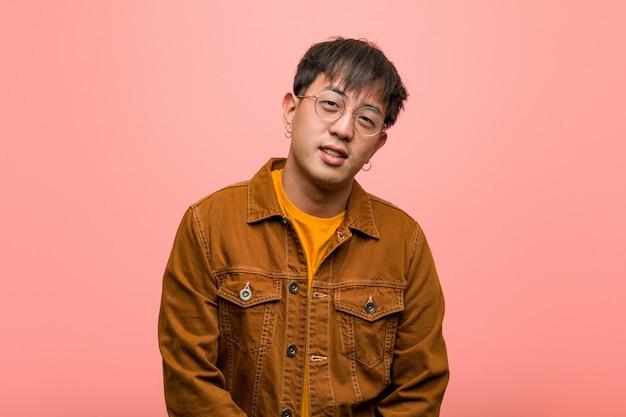 Junger chinesischer mann, der eine jacke freundlich mit einem großen lächeln trägt