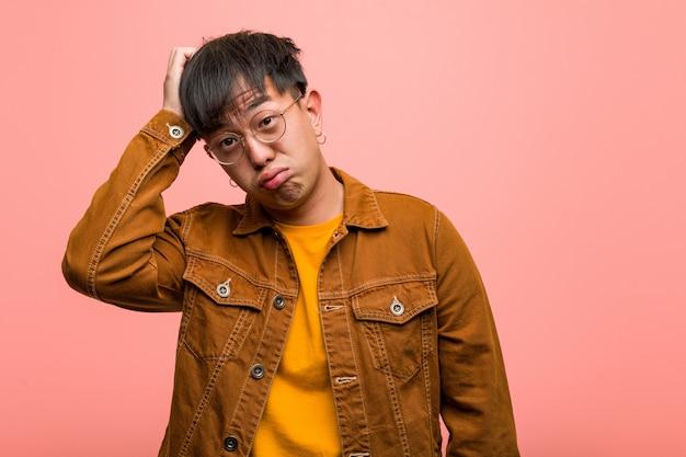 Junger chinesischer mann, der eine jacke gesorgt und überwältigt trägt