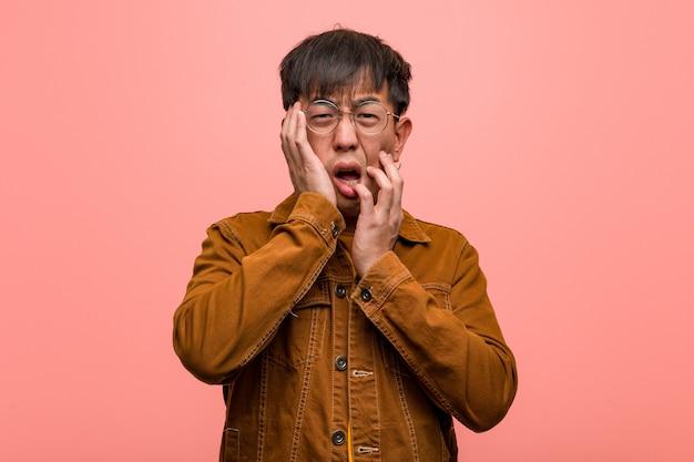 Junger chinesischer mann, der eine jacke hoffnungslos und traurig trägt