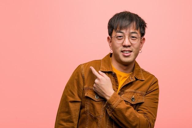 Junger chinesischer mann, der eine jacke lächelt und auf die seite zeigt trägt