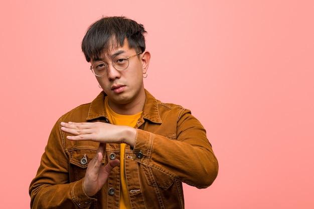 Junger chinesischer mann, der eine jacke trägt, die eine auszeitgeste tut