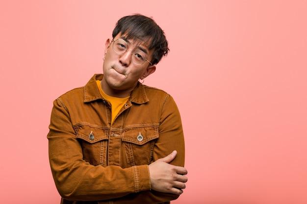 Junger chinesischer mann, der eine jacke trägt, die über eine idee nachdenkt