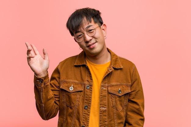 Junger chinesischer mann, der eine jacke tut eine geste des sieges trägt