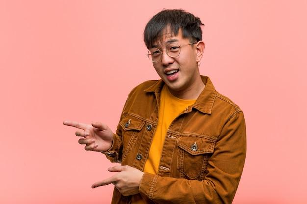 Junger chinesischer mann, der eine jacke zeigt auf die seite mit dem finger trägt
