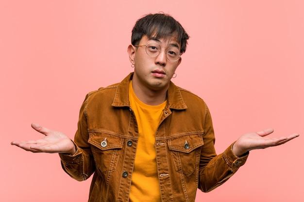 Junger chinesischer mann, der eine jacke zweifelt und schultern zuckt trägt