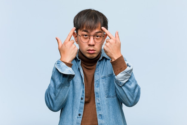 Junger chinesischer mann, der eine konzentrationsgeste tut