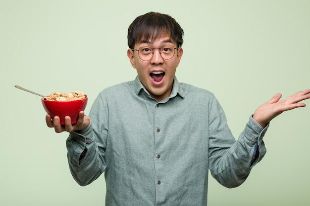 Junger chinesischer mann, der eine müslischüssel isst