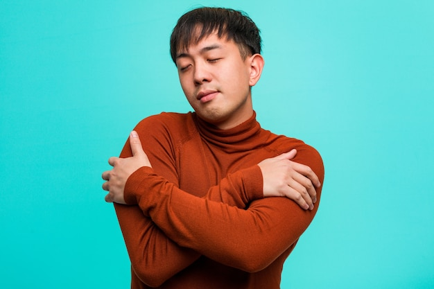 Junger chinesischer mann, der eine umarmung gibt