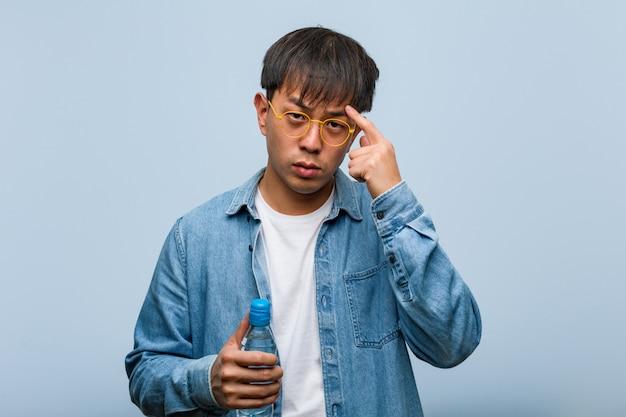 Junger chinesischer mann, der eine wasserflasche denkt an eine idee hält