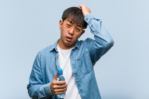 Junger chinesischer mann, der eine wasserflasche hält, besorgt und überwältigt