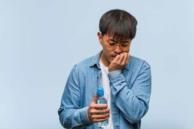 Junger chinesischer mann, der eine wasserflasche hält, die nägel beißt, nervös und sehr ängstlich