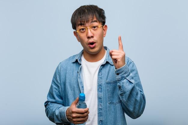 Junger chinesischer mann, der eine wasserflasche hat eine großartige idee, konzept der kreativität hält