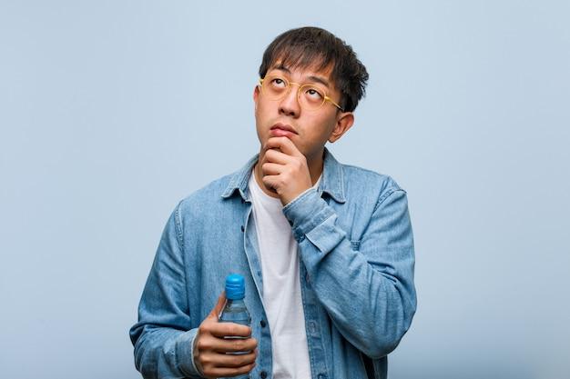 Junger chinesischer mann, der eine wasserflasche zweifelnd und verwirrt hält