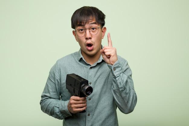 Junger chinesischer mann, der eine weinlese hat eine großartige idee, kreativität hält